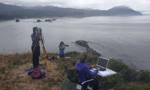 Survey site at Graveyard bluff above Port Orford. Florence van Tulder on laptop, Sarah Wiesner is on theodolite, and Cricket Carine is on camera duty. Credit : Cory Bantam