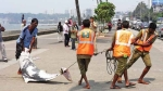 Workers drag the dolphin carcass (Ed Sibylline : a Indo-pacifi humpbacked dolphin) at Marine Drive promenade on Friday (Pradip Patade)
