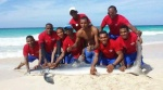 A shark (pictured) died after a group of tourists and lifeguards (pictured) in the Dominican Republic raced into the water to drag it back to shore